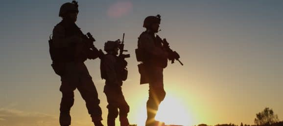 Squad of Three Fully Equipped and Armed Soldiers Standing on Hill in Desert Environment in Sunset Light